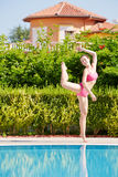 Woman does sport exercises on poolside Royalty Free Stock Images