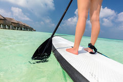 Woman does stand up paddle boarding on the ocean in Maldives. Light water sport on vacation Royalty Free Stock Photo