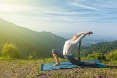 Woman does yoga asana Anjaneyasana in mountains Stock Image