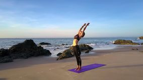 Woman Does Yoga on Clean Beach against Blue Sky. Wonderful panorama joyful young woman in black does yoga on clean morning beach against blue sky stock video footage