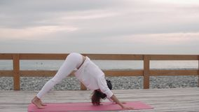 Woman does yoga poses outside in nature. stock footage