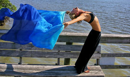Woman does yoga in the sun. Looking down on a beautiful fit young woman as she does a yoga stretch on a dock facing the sun with blue silk cloth flowing out Stock Images