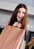 Woman doesn't let paper bags slip out of her hands. Woman doesn't want to let paper bags with gifts slip out of her hands Royalty Free Stock Image
