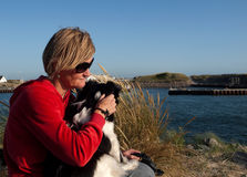 Woman with dog. Sitting by the Water Royalty Free Stock Images