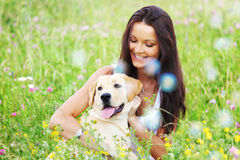 Woman and dog. Woman and she lablador dog in green grass Royalty Free Stock Images