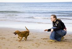 Woman And Dog. Woman Playing With Dog On The Beach Royalty Free Stock Photos
