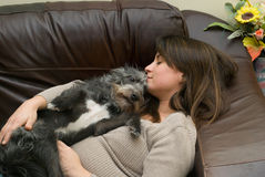 Woman and dog. A pretty young woman asleep with her scruffy dog royalty free stock image