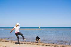 Woman and dog. Woman at sea pitching ball and running dog Royalty Free Stock Photos