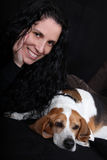 Woman with dog. A portrait of a beautiful woman with her pet dog of Beagle breed, on black background Royalty Free Stock Photography