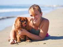 Woman and dog on the beach stock photo