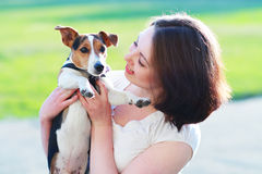 Woman with dog. Woman beautiful young happy with dark hair holding small dog Jack Russell Terrier Royalty Free Stock Image