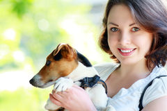 Woman with dog. Woman beautiful young happy with dark hair in striped sweater holding small dog Jack Russell Terrier Stock Images