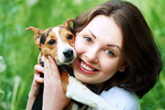 Woman with dog. Woman beautiful young happy with dark hair in striped sweater holding small dog Jack Russell Terrier Royalty Free Stock Images