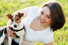 Woman with dog. Woman beautiful young happy with dark hair in white shirt holding small dog Jack Russell Terrier Stock Photo