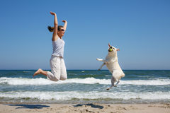 Woman and dog breed Labrador jumping on the beach. On the background of the sea Stock Photo