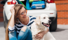 Woman with dog by car full of suitcases. Stock Image