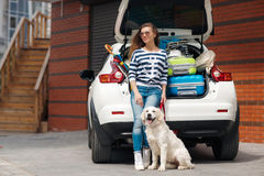 Woman with dog by car full of suitcases. Royalty Free Stock Photography