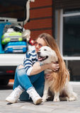 Woman with dog by car full of suitcases. Stock Photos