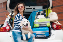 Woman with dog by car full of suitcases. Royalty Free Stock Image