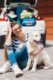 Woman with dog by car full of suitcases. Stock Photography