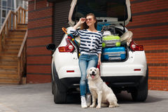 Woman with dog by car full of suitcases. Stock Images