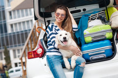 Woman with dog by car full of suitcases. Royalty Free Stock Photo