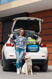 Woman with dog by car full of suitcases. Royalty Free Stock Images