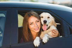Woman and dog in car on summer travel. Vacation with pet concept Royalty Free Stock Photo