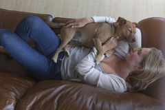 Woman and dog cuddling at home. Ariel view of a woman cuddling her pet dog on a leather sofa royalty free stock photos