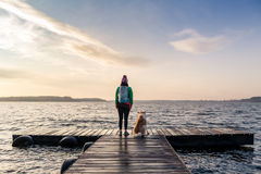 Woman with dog enjoy sunrise at lake, backpacker Stock Photos