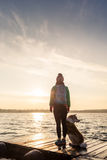 Woman with dog enjoy sunrise at lake, backpacker silhouette Stock Photography