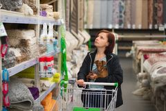 Woman with a dog in her arms and a shopping cart in a carpet store.  royalty free stock photo