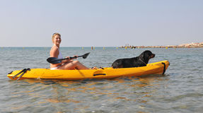 Woman and dog on a kayak Stock Photos