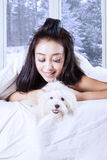 Woman and dog lying under blanket. Portrait of young woman lying under a blanket with maltese dog on the bed Stock Photos