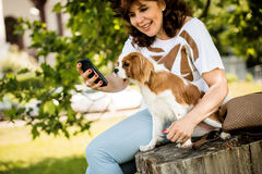 Woman, dog and mobile phone Royalty Free Stock Photography