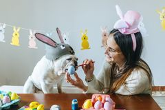 Woman and dog painting easter egg. Stock Image