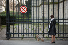 Woman with a dog. Paris, France - January 9, 2012: A woman with a dog standing near the entrance to the park where dog walking is prohibited. Paris suburb of Royalty Free Stock Photos