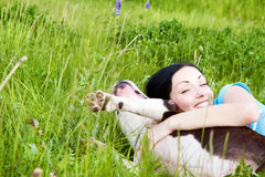 Woman with dog playing in the grass Stock Photo