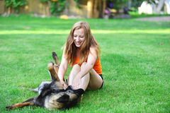 Woman  with dog. Woman playing with dog on grass Stock Photos