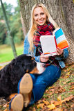 Woman with dog reading book in autumn park Royalty Free Stock Image