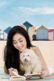 Woman with dog reads book at shore Stock Photography