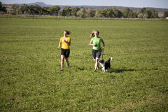 Woman and dog running. Two women running through a field with a dog Stock Images