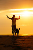 Woman and dog running on beach. Woman and dog running free on beach towards the sun. Sport girl and her pet enjoying freedom and sport together Stock Photo