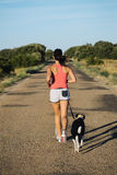 Woman and dog running on country road Stock Photography