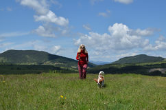 Woman and Dog Running on a Meadow Royalty Free Stock Image