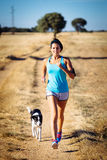 Woman and dog running in rural countryside path. Woman and dog running in country side dirt track. Female runner exercising and training with her pet for cross Royalty Free Stock Photography