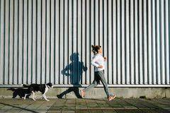 Woman and dog running togheter Royalty Free Stock Image