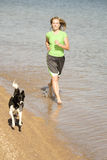 Woman and dog running in water Stock Image