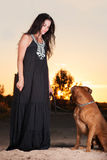 Woman and dog. Woman`s dog looks sunset on the beach Stock Photo