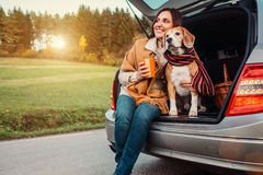 Woman and dog with shawls sits together in car trunk on autumn